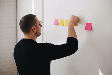 Man putting post-its on a wall